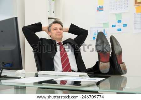 Relaxed Mature Businessman With Feet On Desk At Office - stock photo
