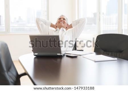 Relaxed mature businessman with hands behind head sitting at desk in office - stock photo