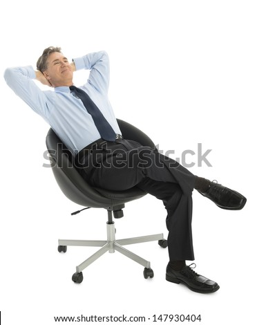 Relaxed mature businessman with hands behind head sitting on office chair against white background