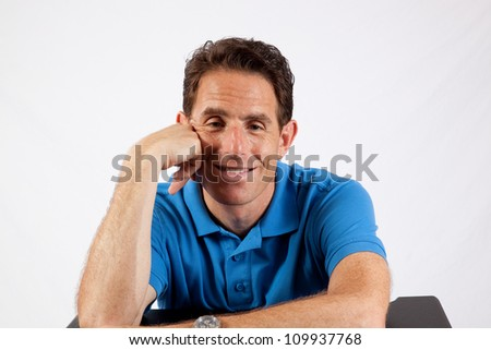 Relaxed mature man holding his hands by his face and with eye contact and a big smile