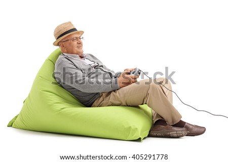 Relaxed mature man sitting on a green beanbag and playing video games with a gamepad isolated on white background - stock photo