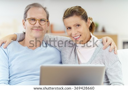 relaxed middle-aged couple embracing and using notebook as they are sitting at home on the sofa