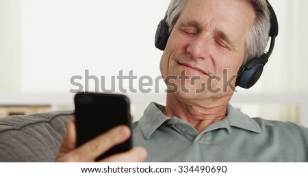 Relaxed middle-aged man listening to music with headphones - stock photo