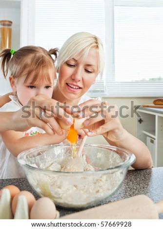 Relaxed mother and child baking cookies in the kitchen - stock photo