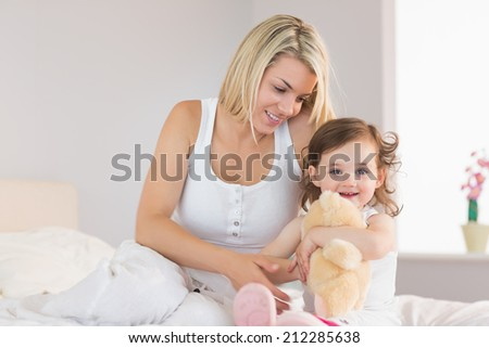 Relaxed mother and young daughter sitting on bed at home