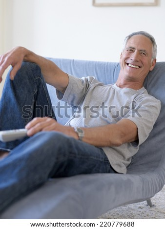 Relaxed portrait of casually dressed man looking to camera holding remote control unit - stock photo