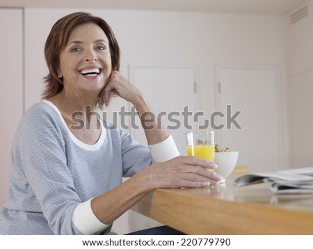 Relaxed portrait of woman at contemporary breakfast bar holding a glass of orange juice - stock photo