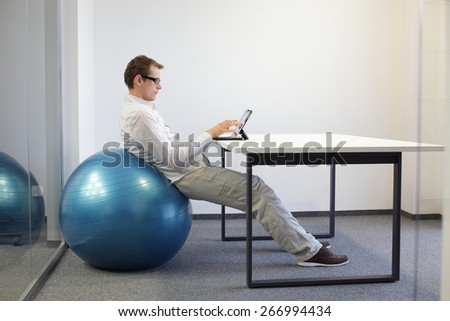 Relaxed position - young man on stability ball at desk working  with tablet - stock photo