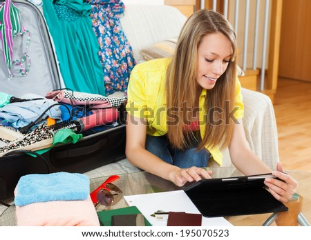 Relaxed pretty female sitting on sofa near luggage and browsing web with tablet