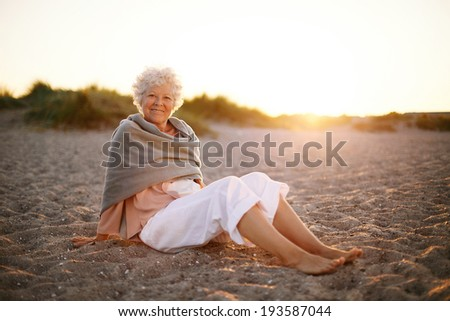 Relaxed retired woman wearing shawl sitting on sandy beach. Old caucasian woman sitting on the beach looking at camera outdoors - stock photo