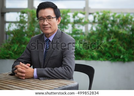 Relaxed Senior Businessman Sitting at Cafe Table