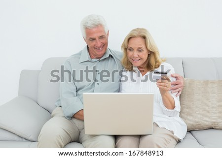 Relaxed senior couple doing online shopping through laptop and credit card on sofa in a house