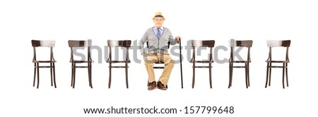 Relaxed senior gentleman sitting on a wooden chair and looking at camera isolated on white background - stock photo