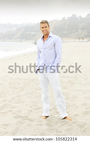 Relaxed smiling man in white pants and elegant blue shirt and bare feet on the beach - stock photo