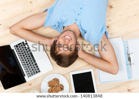 relaxed student lying on the floor between technology - stock photo