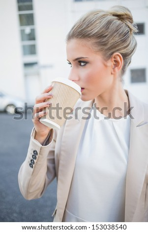Relaxed stylish businesswoman drinking coffee outside on urban background - stock photo
