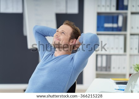 Relaxed successful businessman sitting dreaming in his chair at the office with his hands clasped behind his head and a satisfied smile - stock photo