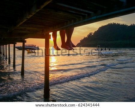 Relaxed tourists hang their legs from a wooden jetty on a tropical island in Thailand at sunset.