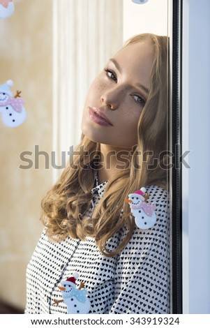 relaxed very pretty girl with freckles posing indoor near window in christmas time with natural make-up long hair and shirt. Some xmas stickers decoration on glass - stock photo
