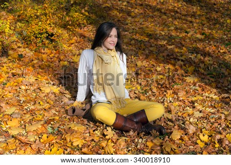 Relaxed woman day dreaming in nature during autumn. She in sitting among leaves and listening MP3 music from smart phone. - stock photo