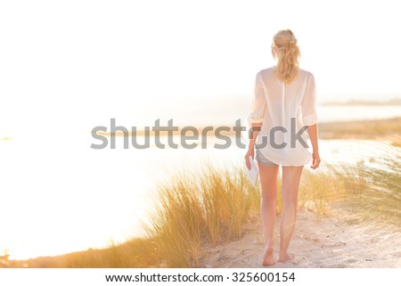 Relaxed woman enjoying freedom and life an a beautiful sandy beach.  Young lady feeling free, relaxed and happy. Concept of happiness, enjoyment and well being.  Enjoying Sun on Vacations. Copyspace. - stock photo