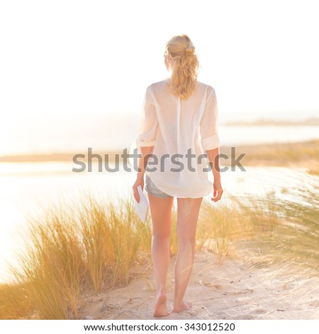 Relaxed woman enjoying freedom and life an a beautiful sandy beach.  Young lady feeling free, relaxed and happy. Concept of happiness, enjoyment and well being.  Enjoying Sun on Vacations. Square. - stock photo