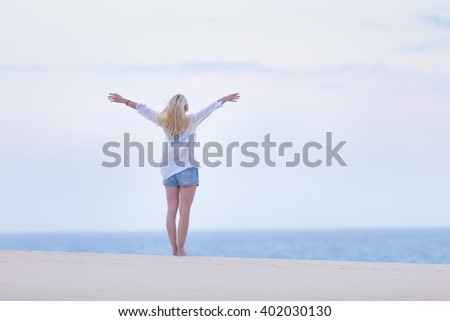 Relaxed woman enjoying freedom feeling happy at beach in the morning. Serene relaxing woman in pure happiness and elated enjoyment with arms raised outstretched up.  - stock photo