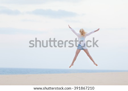 Relaxed woman enjoying freedom, feeling happy. Serene relaxing woman in pure happiness and elated enjoyment, jumping with arms outstretched up. Copy space for text. - stock photo
