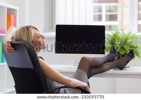 Relaxed woman enjoying successful day at work - stock photo