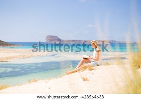 Relaxed woman enjoying sun, freedom and good book an beautiful sandy beach of Balos in Greece. Young lady reading, feeling free and relaxed. Vacations, freedom, happiness, enjoyment and well being. - stock photo