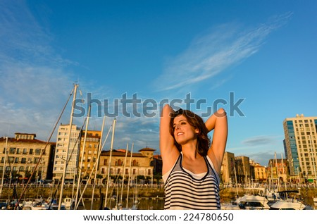 Relaxed woman enjoying the sunset and leisure on european summer travel to Gijon, Asturias, Spain. - stock photo