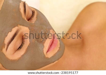 Relaxed woman having her face cleaned with clay mask