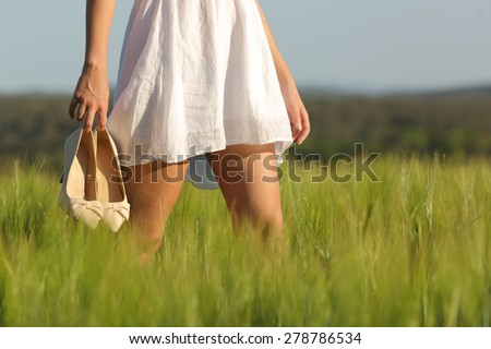 Relaxed woman legs walking in the middle of a field in summer holding high heels - stock photo