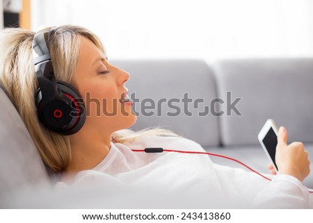 Relaxed woman listening to music on headphones at home - stock photo