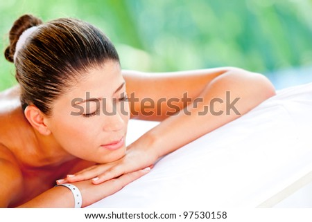 Relaxed woman lying down at an outdoors spa - stock photo