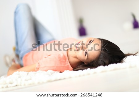 Relaxed woman lying on the floor indoors and smiling - stock photo