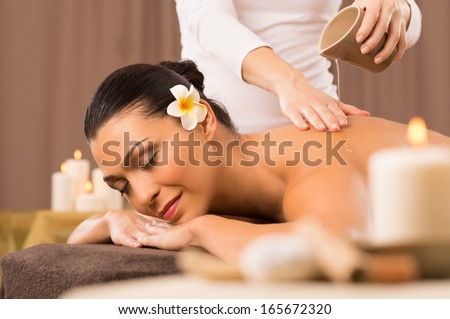 Relaxed Woman Receiving A Back Massage At Health Spa - stock photo