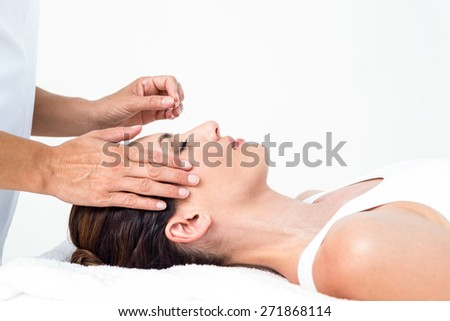 Relaxed woman receiving an acupuncture treatment in a health spa