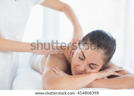Relaxed woman receiving back massage from masseuse at spa