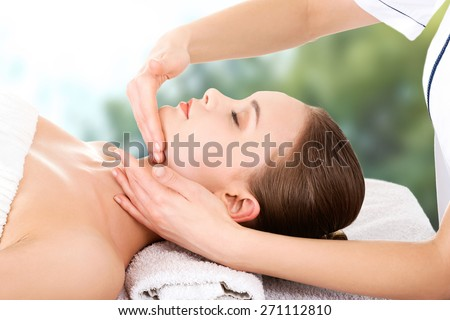 Relaxed woman recieving face massage.