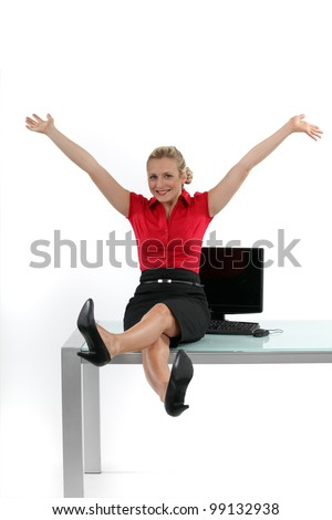 Relaxed woman sitting on her desk - stock photo