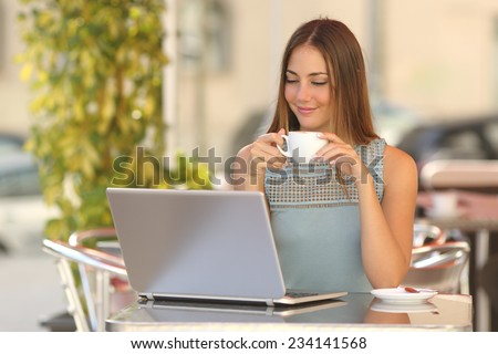 Relaxed woman watching a laptop in a restaurant and holding a cup of coffee