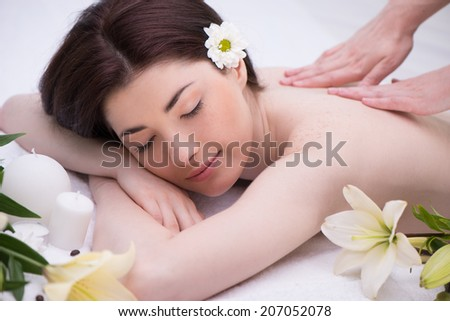 Relaxed woman with flowers in spa center enjoying massage - stock photo