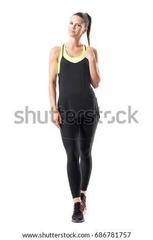 Relaxed young active woman in sportswear spinning ponytail hair and smiling at camera. Full body length portrait isolated on white background.