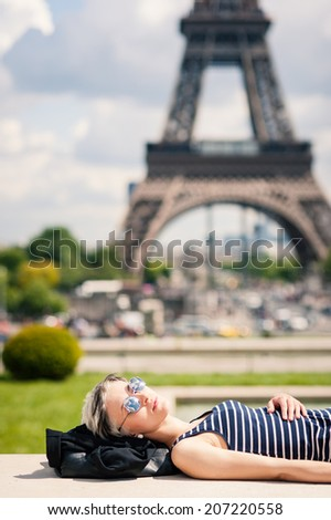 Relaxed young blonde woman portrait laying on the ground in front of the Eiffel Tower. Paris, France.  - stock photo