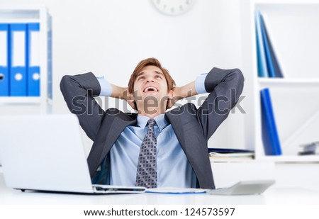 Relaxed young business man happy smile sitting at the desk, handsome businessman relaxing hold hand on head look up