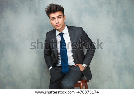 relaxed young business man sitting on chair with hands in pockets , studio shot