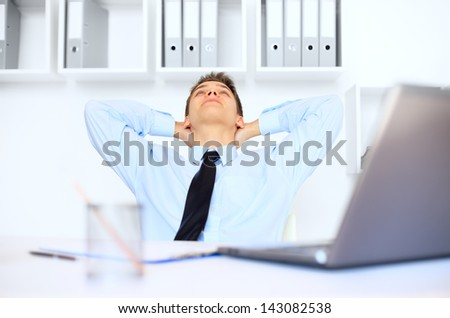 Relaxed young businessman at his workplace in bright office