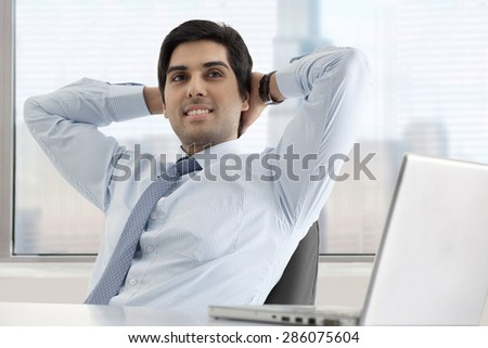 Relaxed young businessman sitting at his desk with laptop - stock photo