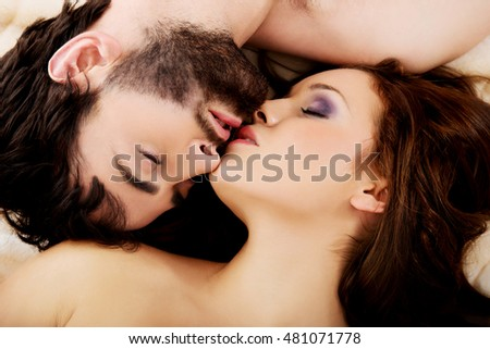 Relaxed young couple kissing in bed.